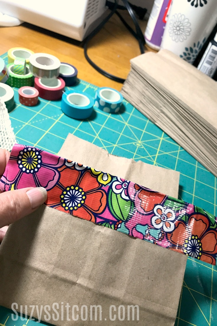 Adding decorative duck tape to the paper bag