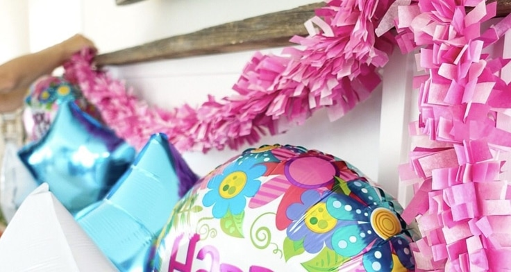 Pink tissue paper garland with birthday balloons.