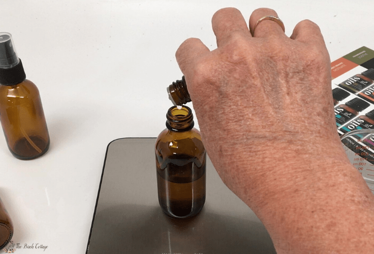 adding lavender essential oil to glass amber bottle
