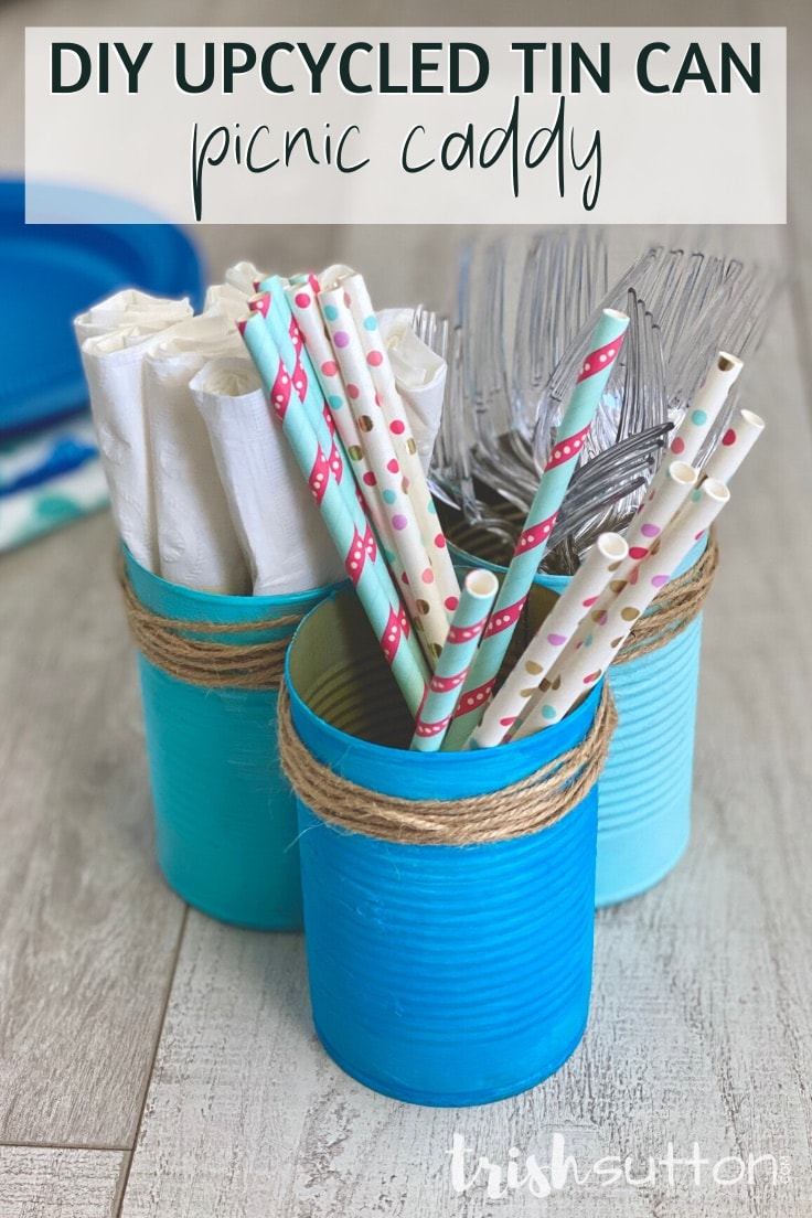 DIY upcycled can picnic caddies filled with straws, napkins & forks on a wood background.
