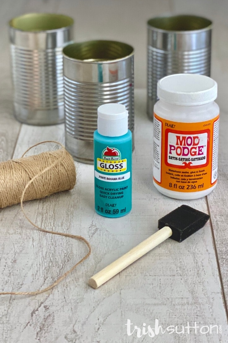 Supplies needed to create a DIY upcycled picnic caddy including cans, paint, glue, jute & a paintbrush.