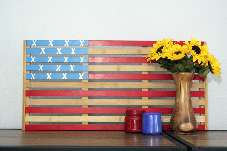 wooden American flag on a bookshelf with a vase of sunflowers and candles