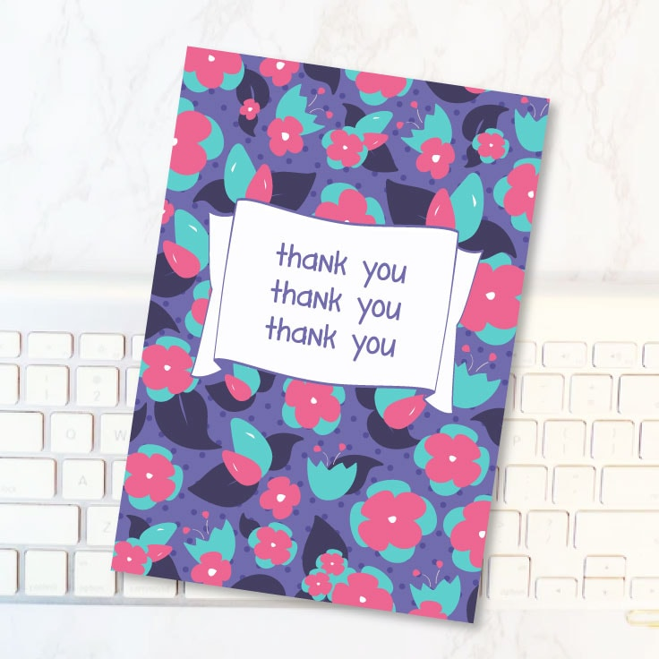 Preview of purple floral thank you card design on desk with computer keyboard.