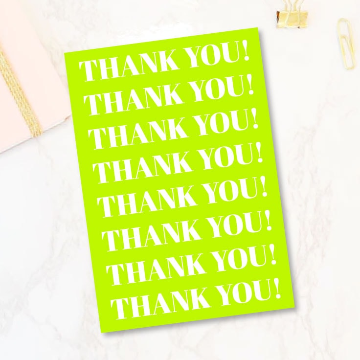 Preview of lime green type thank you card on marble desktop.
