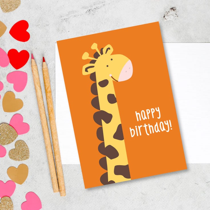Preview of giraffe happy birthday card design on kitchen counter with paper punch out heart confetti and two colored pencils.
