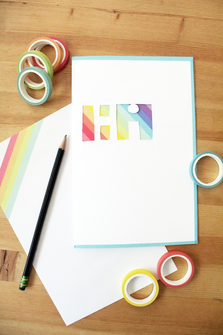 "a card with ""Hi"" cutout of the front piece shows rainbow washi tape behind the lettering"