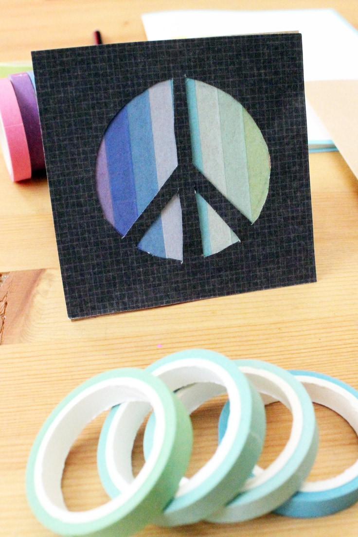 a black card with a peace sign cut out shows blue ombre washi tape behind