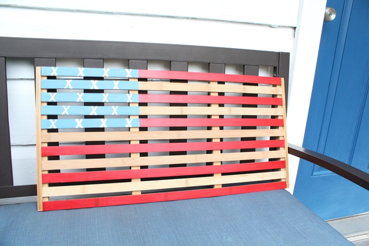 wooden American flag sitting on a bench on a porch