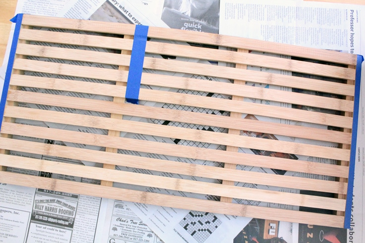 wooden mat marked with blue tape on the edges and one-quarter of the slats
