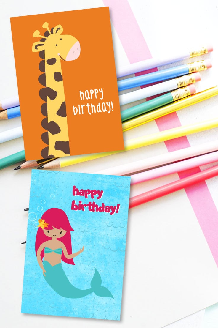 Giraffe happy birthday card design and mermaid happy birthday card design on top of pencils in various colors.