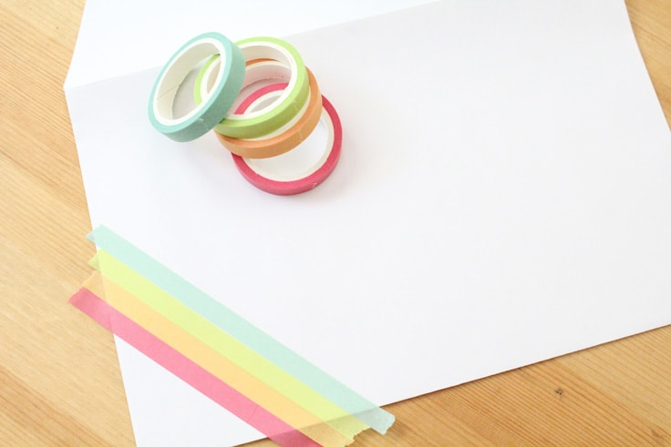 pink, orange, green, and blue washi tape adorn the corner of a white envelope