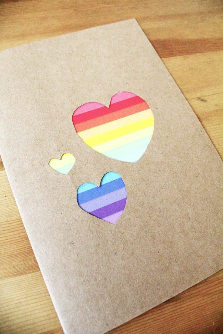 3 hearts on a kraft brown card are cutout to show the rainbow washi tape behind