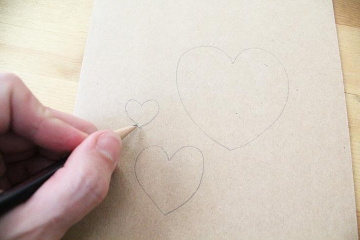 a hand draws three hearts on kraft paper