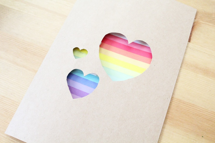 the finished washi tape card shows three heart cutouts with rainbow colors behind