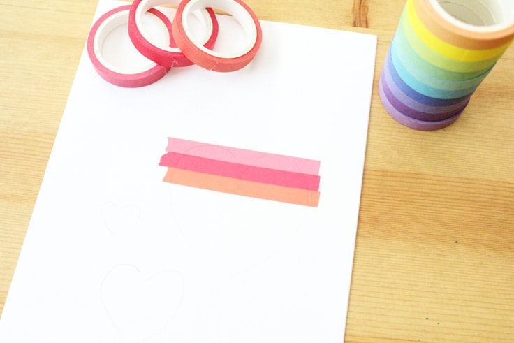 three strips of washi tape in shades of pink are stuck to white card stock