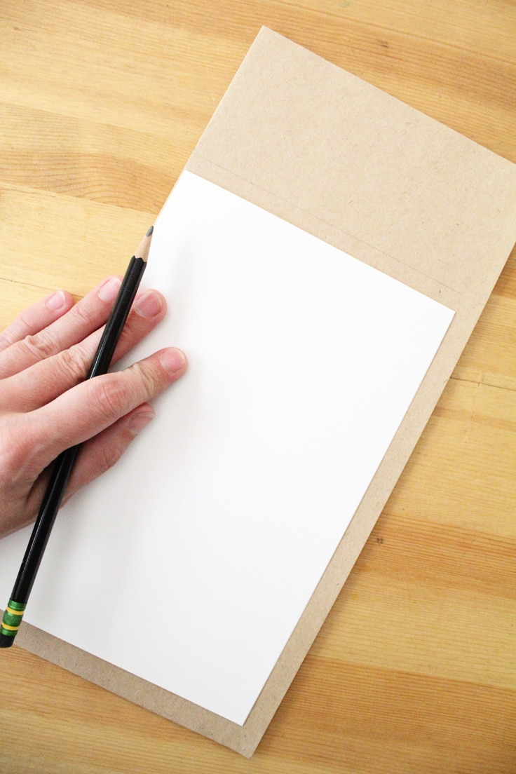 a hand holds a pencil and traces white paper against kraft brown paper