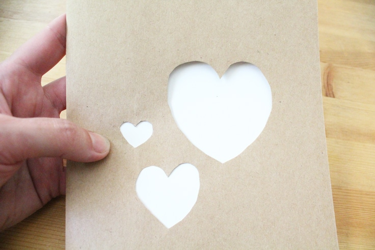 three hearts cut out of kraft paper show the white paper beneath