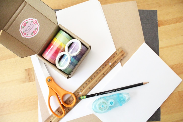 stack of supplies including paper, washi tape, scissors, a ruler, a pencil, and a double-sided adhesive runner