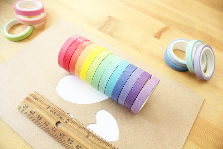 13 rolls of washi tape in solid colors line up to create a rainbow