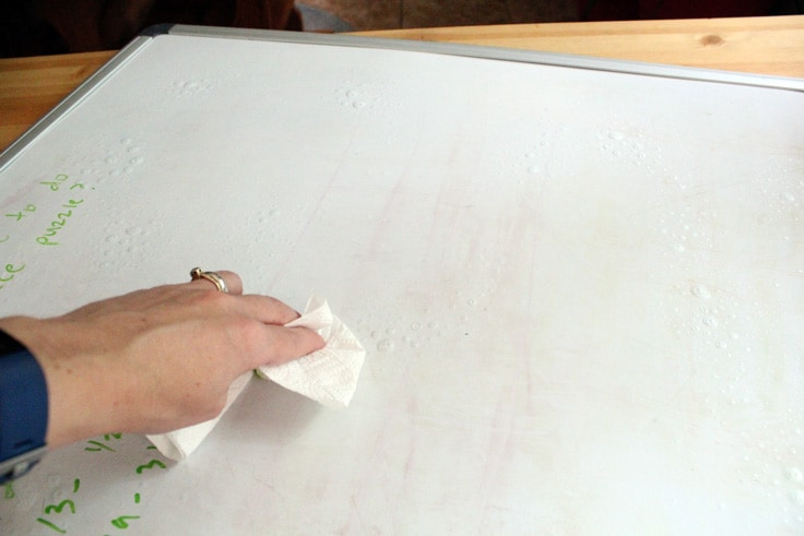 a hand wiping down a white marker board with a paper towel to clean it
