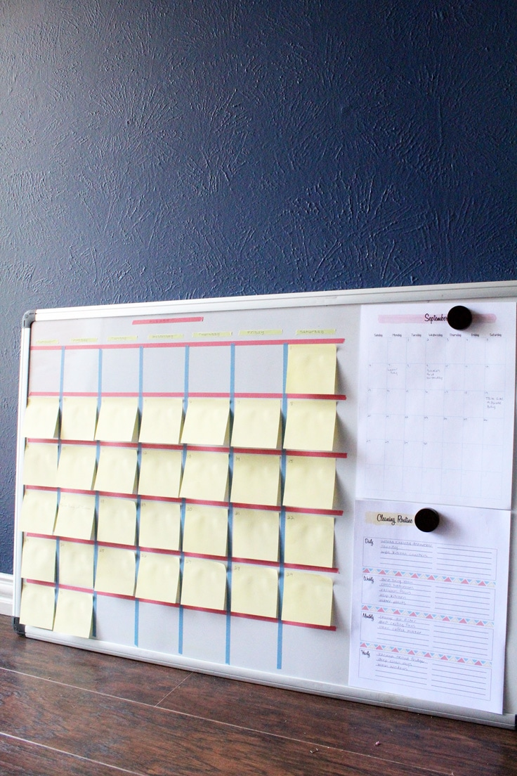 DIY calendar made from washi tape and sticky notes on a white board leaning against a blue wall