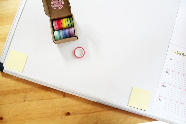 box of washi tape sitting on a blank white dry erase board beside 2 sticky note pads