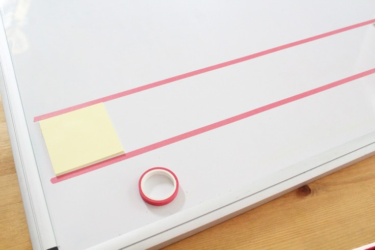 2 rows of washi tape on a dry erase board with a sticky note between them