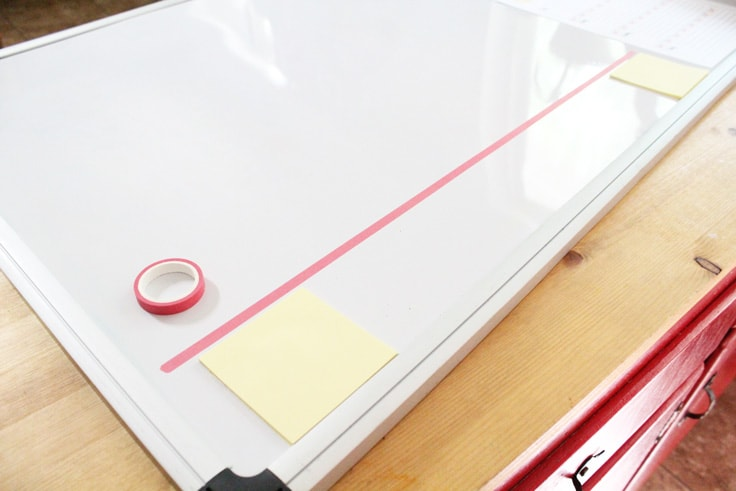 one line of pink washi tape stuck to a dry erase board above 2 sticky notes