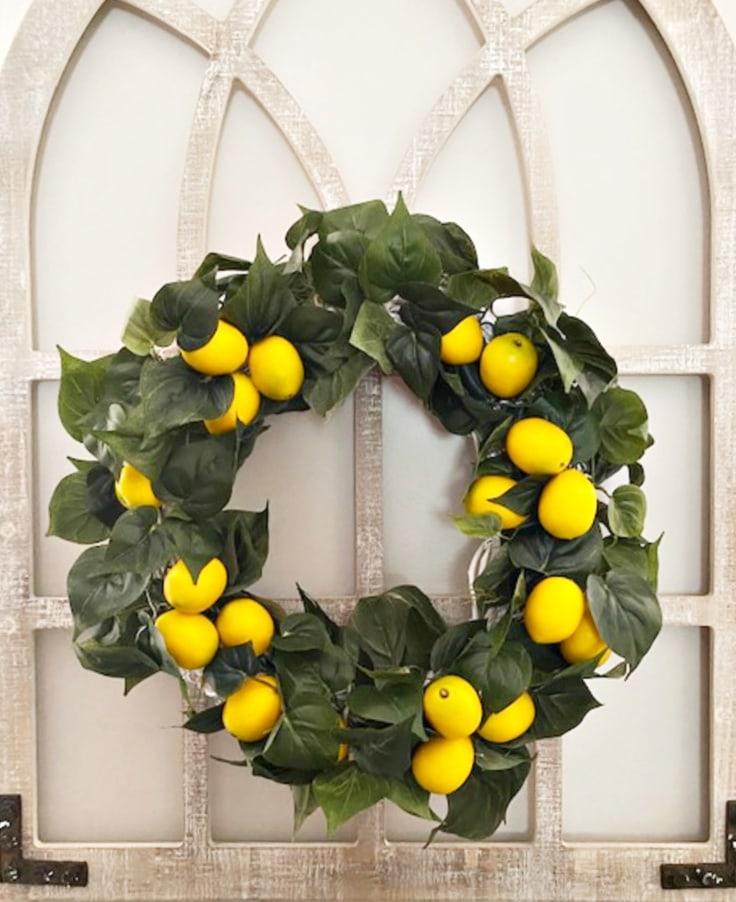 diy lemon wreath shown hanging on arch