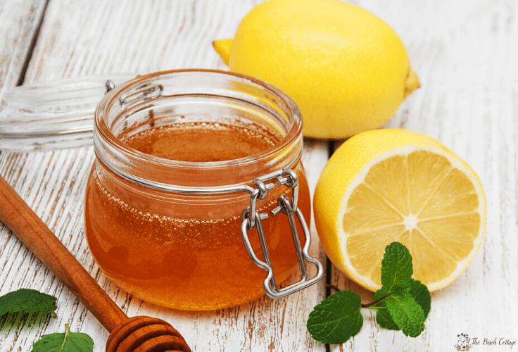 Weck jar of honey with honey dipper and lemons