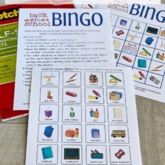 Back to School Bingo Game cards, instructions & pieces on a wood background.