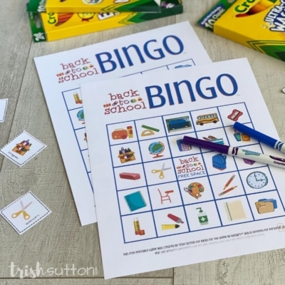 Two Bingo cards on a wood background surrounded by game pieces and markers.
