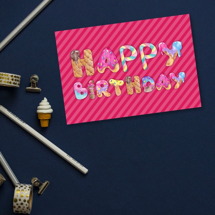 Preview of pink happy birthday card on dark desk with washi tape and stationery items.