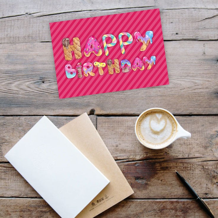 Preview of pink happy birthday card on wooden table with journals, coffee cup and pen.