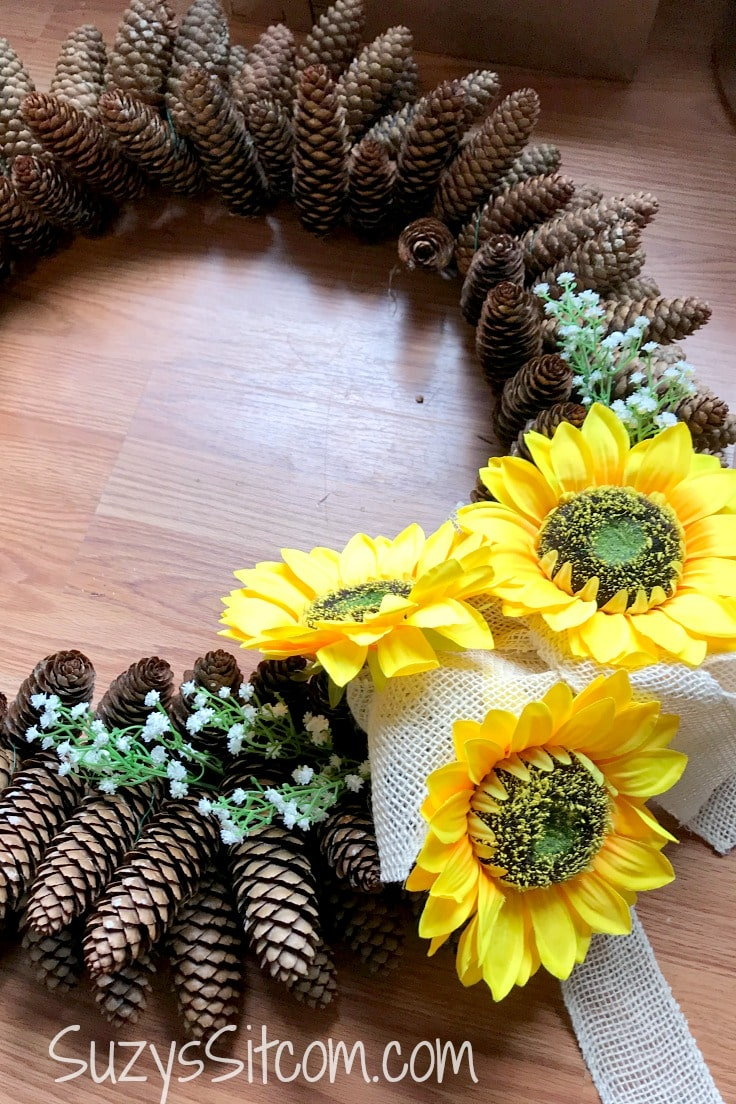 Silk sunflowers and a white bow on a pine cone wreath