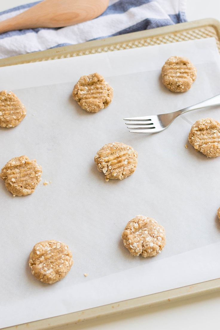Oatmeal cookies that are ready to be baked! Rolling the cookie batter into spheres and flattening them with forks for the perfect shape.