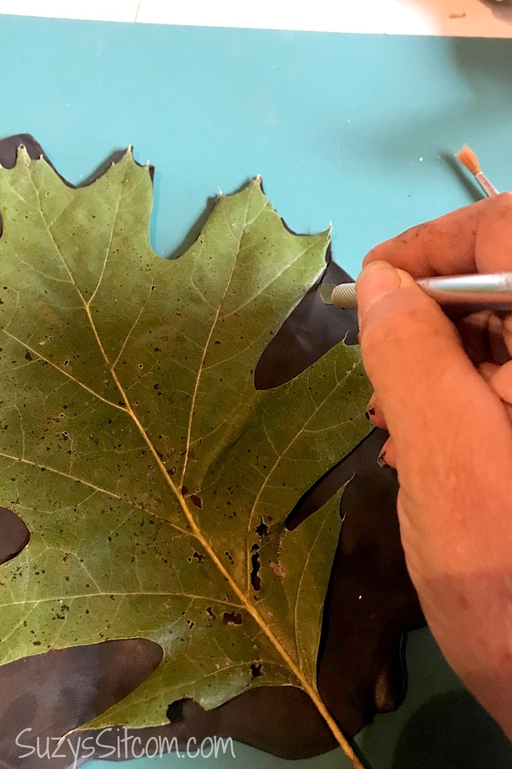 Cutting clay out while using a leaf as a template