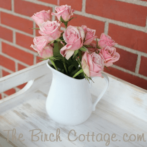 chalk painted wood tray with pink roses in a white ceramic pitcher