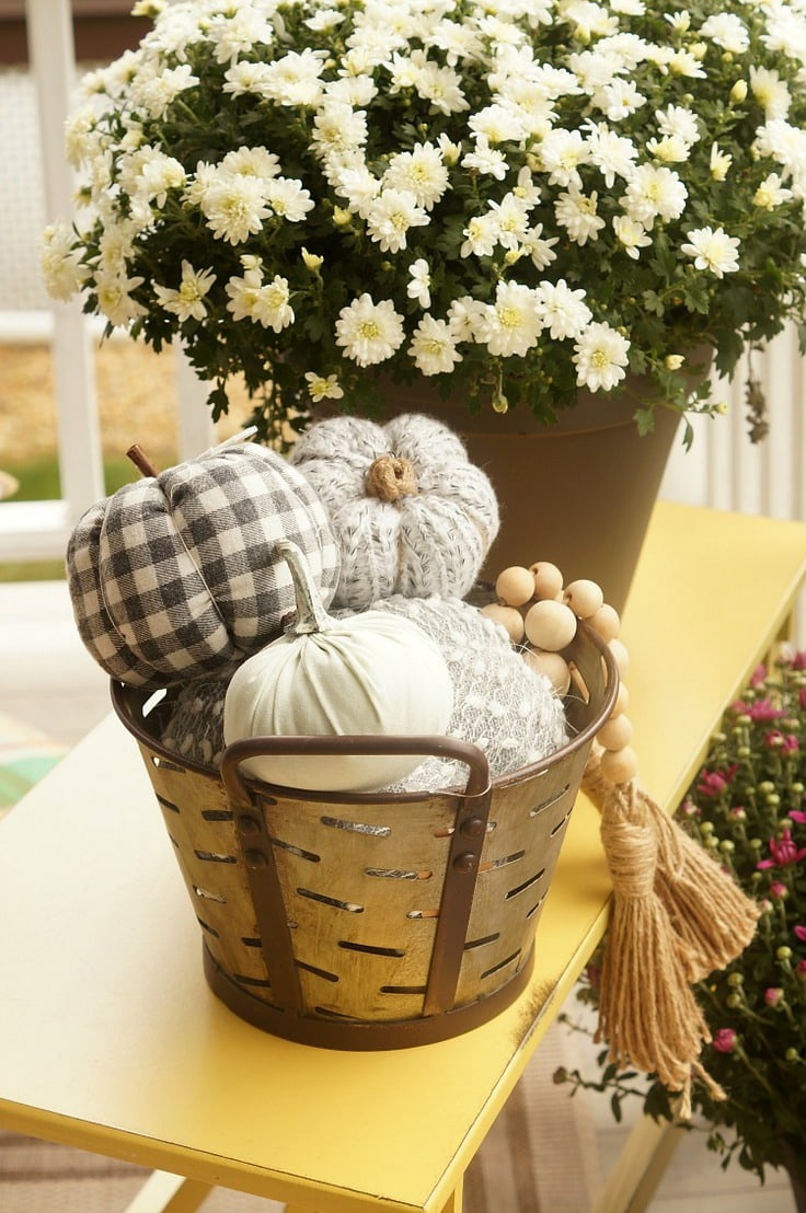 A tin bucket with fabric pumpkins and wood beads