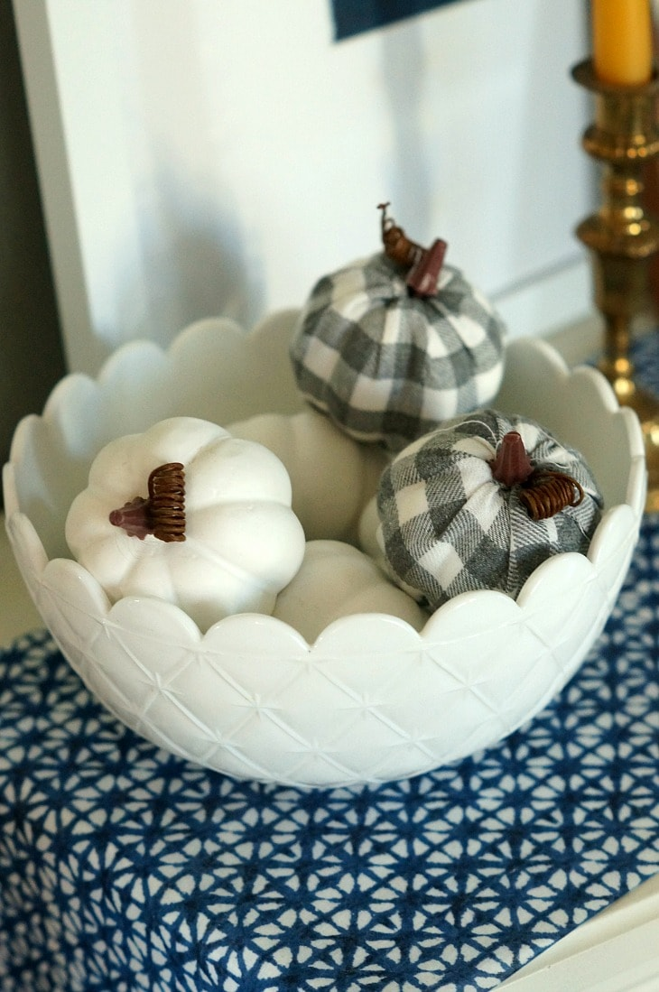 A white bowl filled with small white decor pumpkins and 2 buffalo check pumpkins