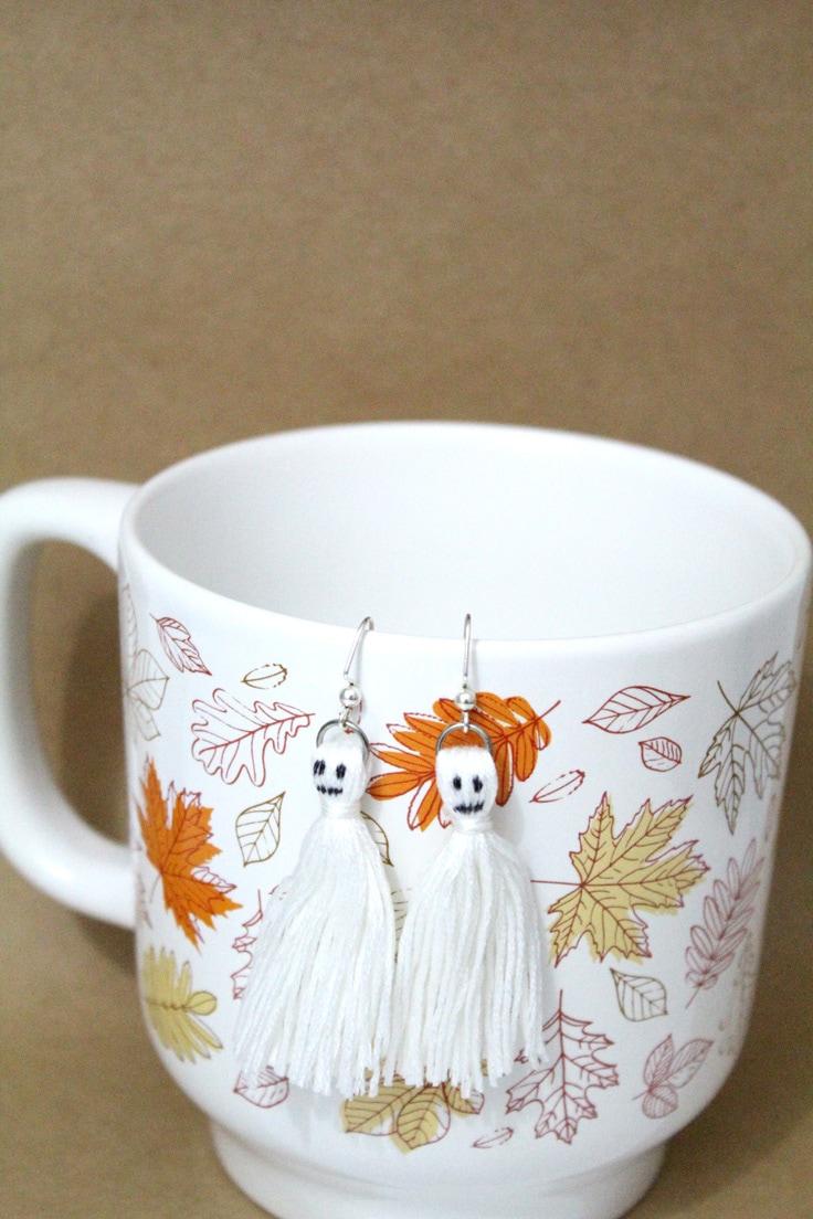DIY Halloween ghost tassel earrings hanging on a fall themed coffee mug