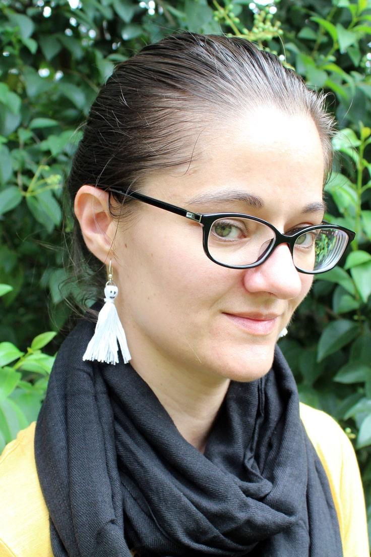 woman wearing white ghost tassel earrings with a black scarf