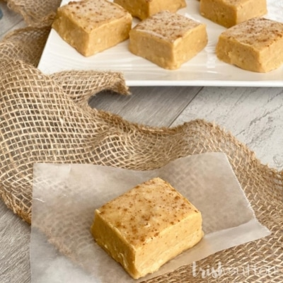 A piece of pumpkin fudge resting on burlap with a plate of fudge in the background.