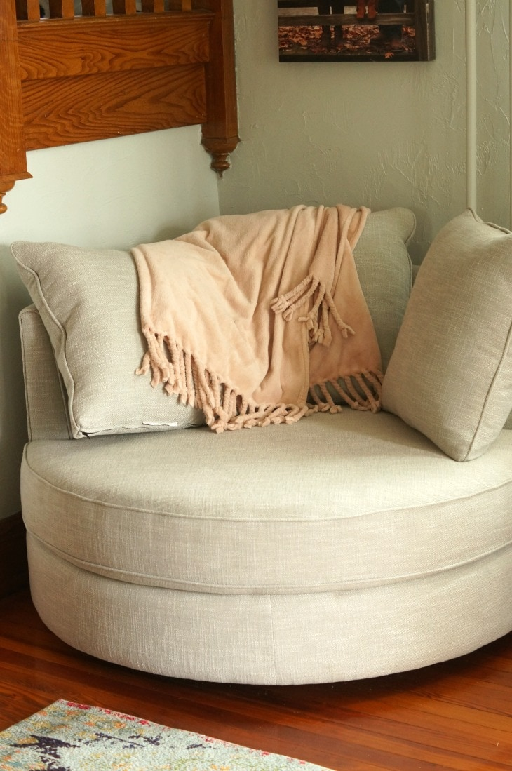A reading chair with an orange blanket