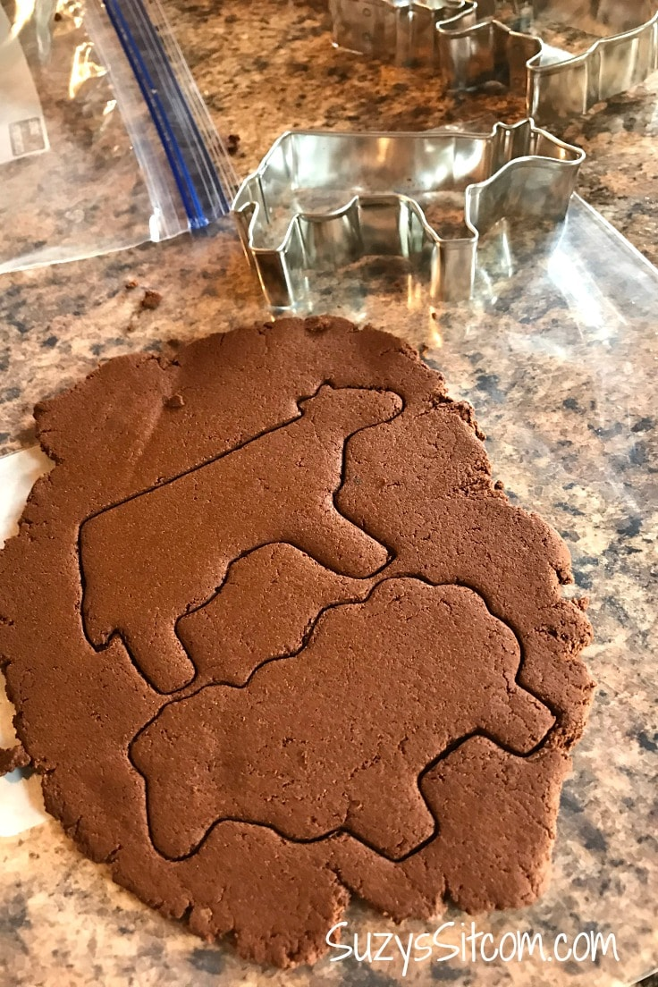 Rolling out cinnamon ornament dough and using cookie cutters to cut out farm animal shapes.