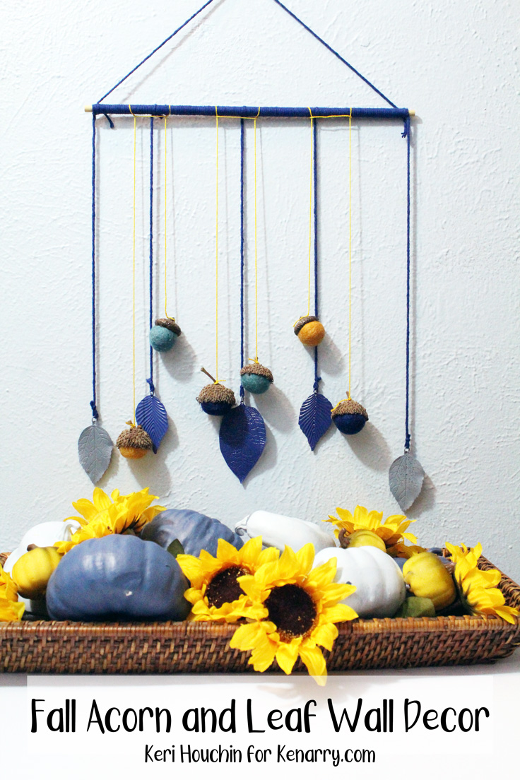 fall wall decor hanging with blue painted leaves and blue and yellow felt acorns with natural caps