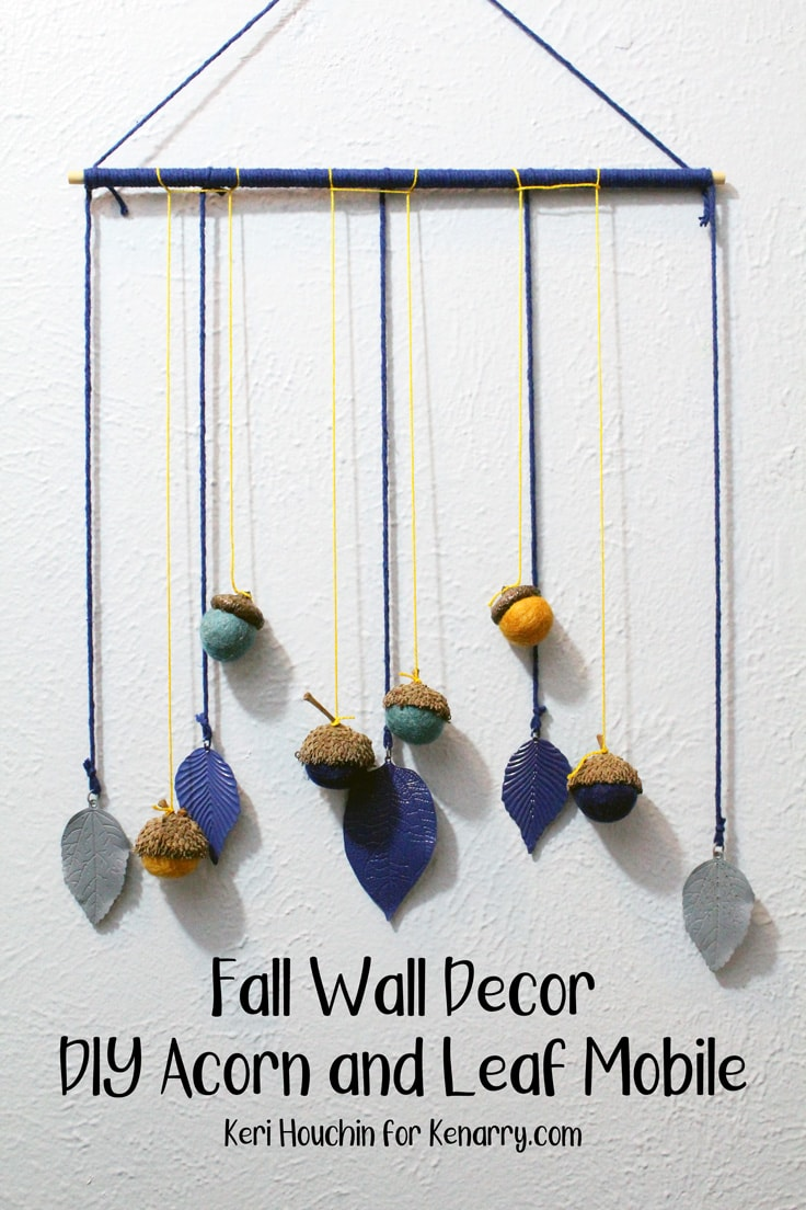 fall wall decor idea with acorns and leaves hanging from a yarn-wrapped dowel