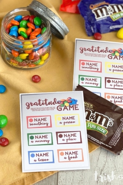 Gratitude game cards with M&Ms on a yellow fabric background.