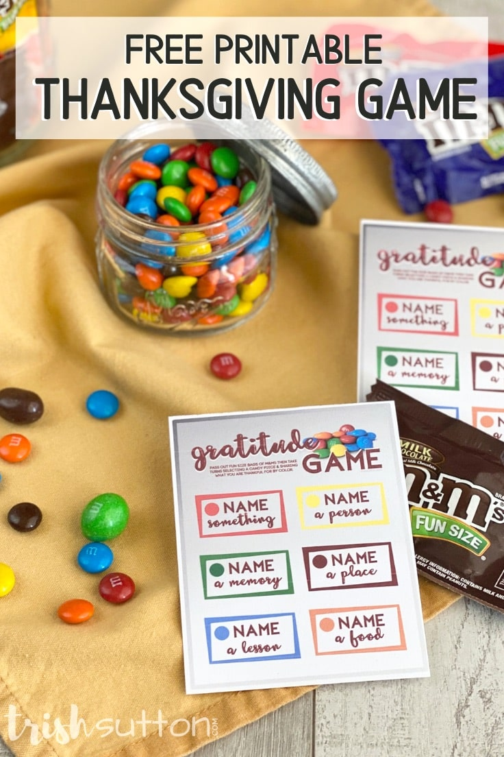 Gratitude game cards with a jar of M&Ms on a yellow fabric background.