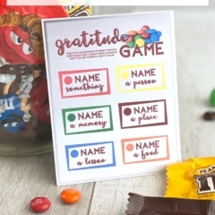 Thanksgiving activity gratitude game card standing against a jar of M&Ms on a wood backdrop.